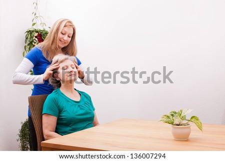 pretty Young woman massaging female seniors scalp - stock photo