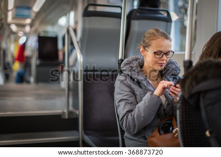 Pretty, young woman on a streetcar/tramway, during her commute to work. Using her smartphone. (color toned image; shallow DOF) - stock photo
