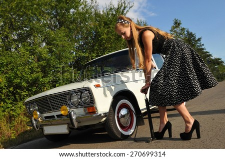 Pretty young woman outdoor at summer trying to pump tyre of white old car - stock photo