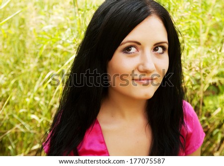 pretty young woman outdoor in the grass in summertime