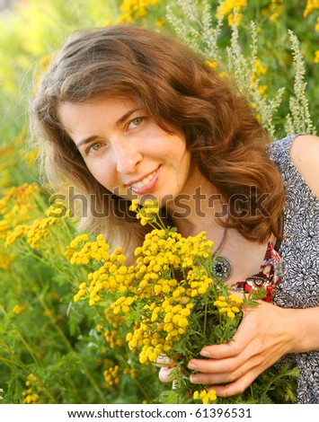 pretty young woman outdoor in the grass in summertime - stock photo