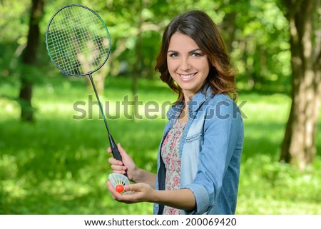 Pretty, young woman playing badminton in a city park on a lovely summer day - stock photo