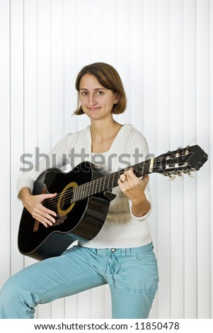 Pretty young woman playing the guitar. - stock photo