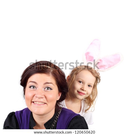 pretty young woman playing with the cute little child dressed as a hare - stock photo