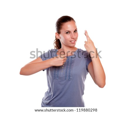 Pretty young woman pointing to her left and crossing her fingers on blue blouse on isolated background - stock photo