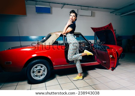 Pretty young woman posing in vintage garage  - stock photo