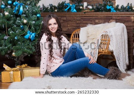 Pretty young woman posing near the christmas tree and fireplace - stock photo