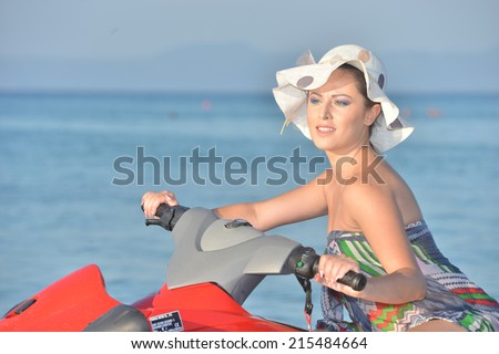 Pretty young woman posing on a jet ski  - stock photo