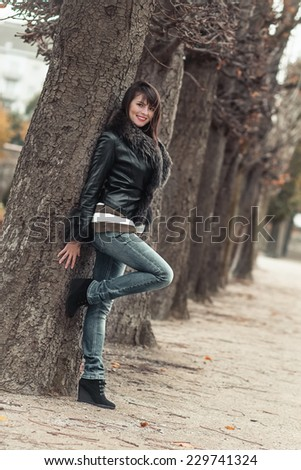 Pretty young woman posing outdoors. Attractive girl standing and wearing fur,  autmn day - stock photo