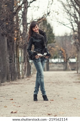 Pretty young woman posing outdoors. Attractive girl standing and wearing fur,  autumn day - stock photo