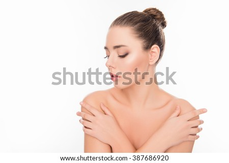 Pretty young woman posing with crosed on shoulders hands and closed eyes - stock photo