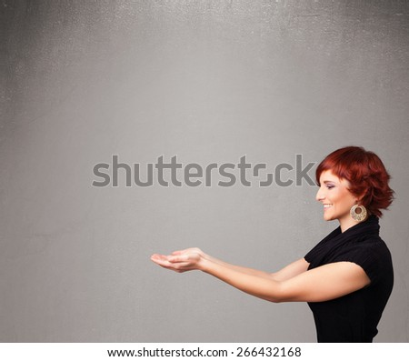Pretty young woman presenting an empty copy space - stock photo