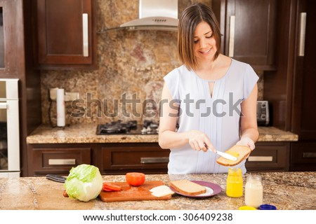 Pretty young woman putting some mustard on a bread and preparing a sandwich for lunch - stock photo