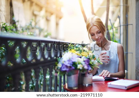 Pretty young woman reading book while sit at terrace table on her balcony, attractive young girl reading book while drinking coffee at sunny day sitting on balcony, sunny morning on beautiful balcony - stock photo
