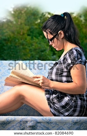 pretty young woman reading magazine