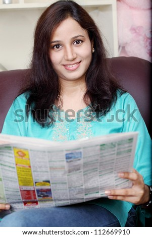 Pretty young woman reading newspaper at home - stock photo