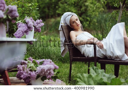 Pretty young woman resting after spa procedures in the garden with lilac flower
