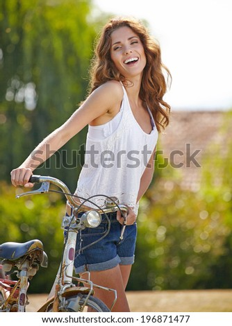 Pretty young woman rwith old bike in a country road.