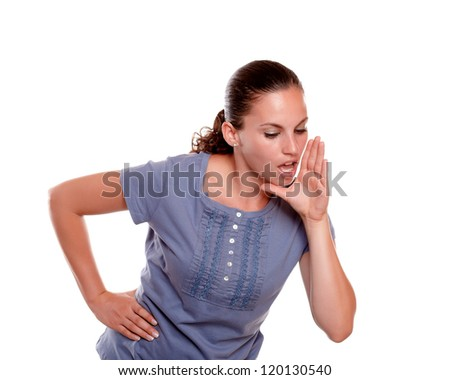 Pretty young woman screaming something down on blue shirt on isolated background - copyspace - stock photo