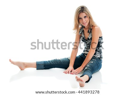Pretty young woman seated on the floor isolated on a white background.