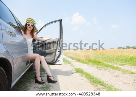 Pretty young woman sit in open car