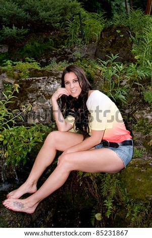 pretty young woman sits in garden