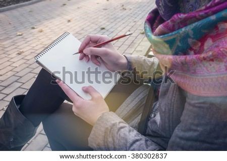Pretty young woman sitting and making notes to her diary, notebook