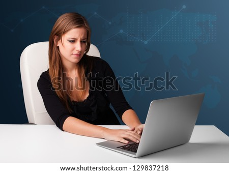 Pretty young woman sitting at desk and typing on laptop