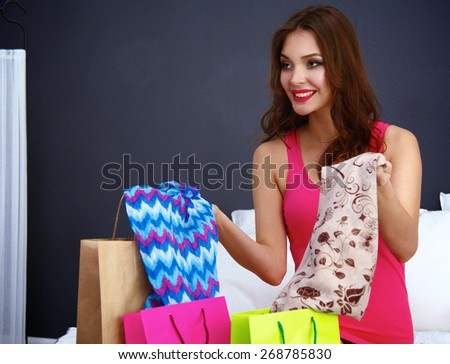 Pretty young woman sitting bed with shopping bags  - stock photo