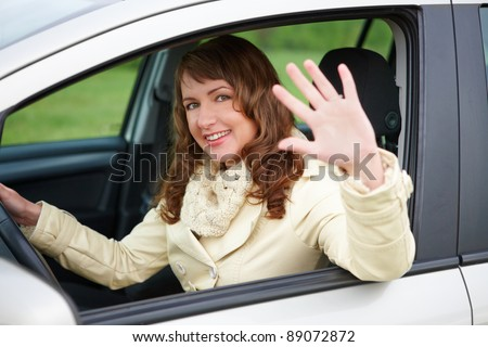 Pretty young woman sitting car looking out of window, waving and smiling