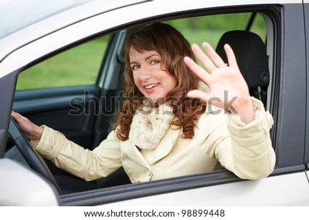 Pretty young woman sitting car looking out of window, waving and smiling - stock photo