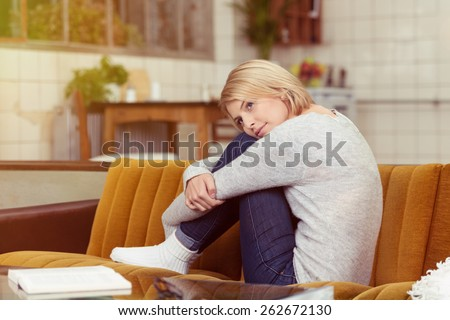 Pretty young woman sitting daydreaming on the sofa with her head resting on her drawn up knees staring up into space with a smile - stock photo