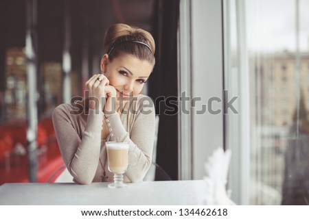 pretty young woman sitting in a cafe with a cup of coffee latte - stock photo