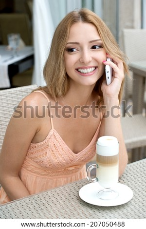 pretty young woman sitting in a cafe with a cup of coffee latte and on the phone at a cafe