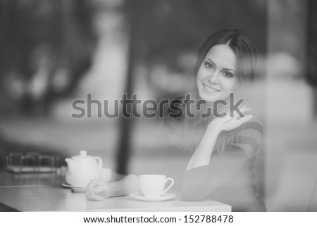 pretty young woman sitting in a cafe with a cup of tea