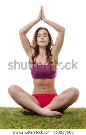 pretty young woman sitting in a yoga pose on the grass with her legs crossed and eyes closed - stock photo