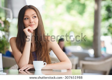 pretty young woman sitting in cafe with a cup of tea or coffee outdoor. Charming woman in a restaurant. Woman with coffee - stock photo