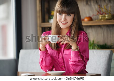pretty young woman sitting in cafe with a cup of tea or coffee outdoor. Charming woman in a restaurant. Woman with coffee. Beautiful girl in restaurant. Woman portrait indoors. - stock photo