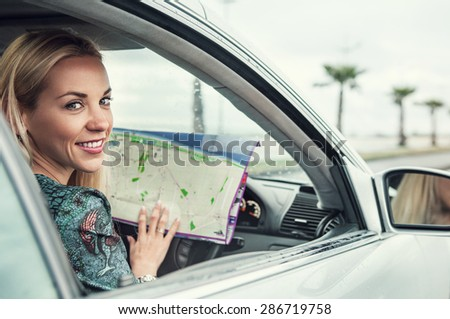 Pretty young woman sitting in car with a roads map - stock photo