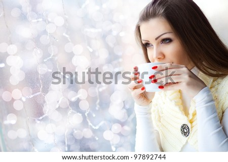 pretty young woman sitting in the cafe with a cup of coffee - stock photo