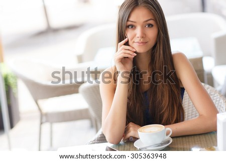 pretty young woman sitting in the cafe with a cup of tea or coffee. Charming woman in a restaurant.
