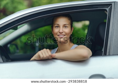 Pretty Young Woman Sitting Inside the Car, Smiling at the Camera While Leaning on the Open Window - stock photo