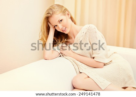 Pretty young woman sitting on a sofa at home and smiles. Interior. - stock photo