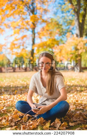 Pretty Young Woman Sitting on Grassy Ground with Dried Leaves  Listening Music on Ipod with Headset. Looking at Camera. Isolated on Nature Background. - stock photo