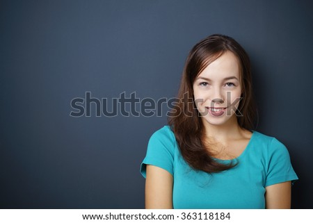 Pretty Young Woman Smiling at the Camera Against Dark Gray Wall with Copy Space on the Left Side. - stock photo