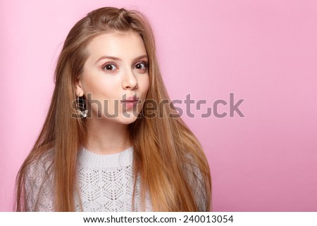 Pretty young woman smiling funny at the pink background. Studio shot. Valentines Day, holidays, happiness, International Women's Day - stock photo