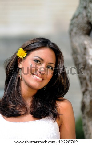 pretty young woman smiling with dandelion in her hair seated