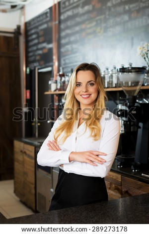 Pretty young woman standing behind the counter of his cafe
