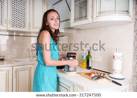 Pretty young woman standing cooking in her kitchen grating cheese for her recipe with a plate of raw chopped meat standing ready alongside - stock photo