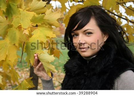 Pretty young woman standing near maple in autumn park